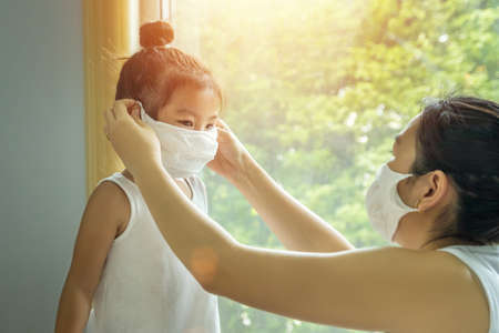 Asian family with children in face mask, mother prepare to put face mask on her kid before leaving house to go school for prevent germs during the coronavirus or covid-19 outbreak. new normal concept Stockfoto