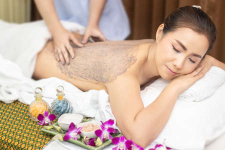 beautiful young Asian woman relaxing with hand massage making mud clay mask and salt scrub on naked back body skin by masseur at beauty spa salon treatment. relaxing massage