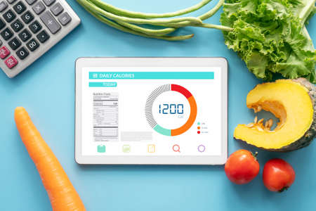 Calories counting , diet , food control and weight loss concept. tablet with Calorie counter application on screen at dining table with fresh vegetable and calculator. healthy eating lifestyle