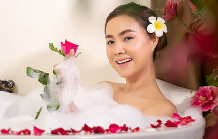 relaxing beautiful Asian woman pampering her body in water in a spa bathtub with white foam bubble of soap and rose petals. recreational pursuit Stockfoto