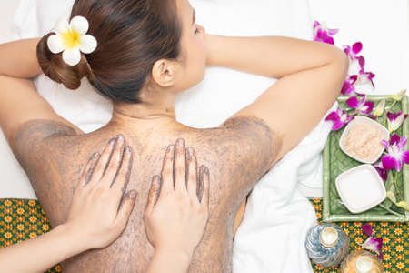 beautiful young Asian woman relaxing with hand massage making mud clay mask and salt scrub on naked back body skin by masseur at beauty spa salon treatment. relaxing massage, top view