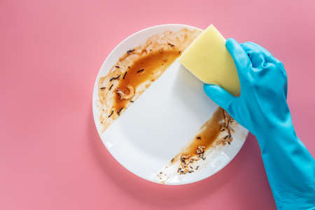hand in blue rubber glove hold yellow cleaning sponge to clean up and washing food stains and dirt on white dish after eating meal isolated on pink background. cleaning, healthcare, sanitation at home Stock fotó