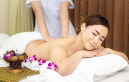 beautiful young Asian woman relaxing with hand massage on naked back body by masseur at beauty spa treatment. relaxing massage