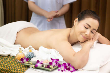beautiful young relax Asian woman laying on massage bed with naked back body, masseur prepare oil massage at back side at beauty spa salon treatment Stockfoto