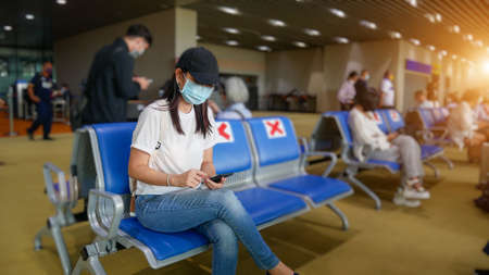 Asian tourist with mobile phone ,wearing hygienic mask, sit on chair with social distancing to prevent pandemic during travel at airport terminal. new normal after coronavirus, covid-19 virus epidemic
