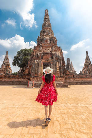 Asian tourist woman in red dress and sun hat from back view, walking through the beautiful history castle and historic temple at Ayutthaya, Thailand during vacation. travel after coronavirus lockdown