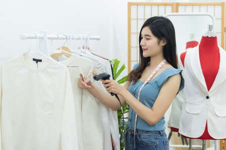 small business owner concept. young happy confident designer Asian woman with tape measure on neck use handheld barcode scanner to shoot at clothing price tag in fashion store workshop studio office