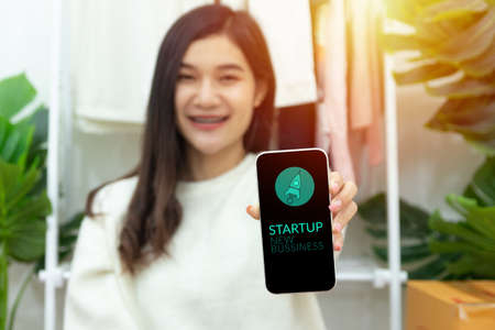 young happy confident small business owner Asian woman showing smartphone with screen display for startup new business with rocket launch icon. business startup, launching of a new company. Stock fotó