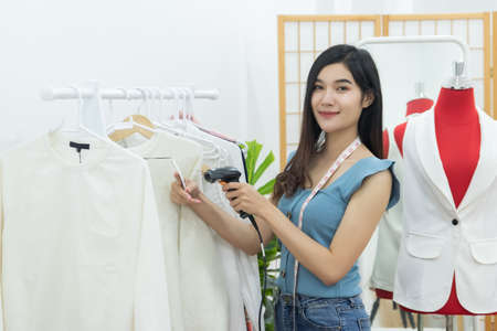 small business owner concept. young happy confident designer Asian woman with tape measure on neck use handheld bar code scanner to shoot at clothing price tag in fashion store workshop studio office