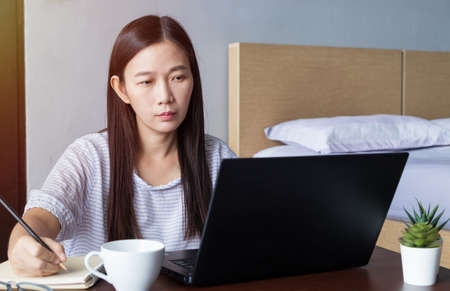 new normal, work from home, study online, homeschooling, distance education. Asia student woman study online, listen lecture via laptop at home during   infection epidemic spreading