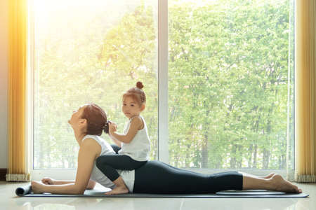 Asian mom practice Cobra yoga pose, work out at home with a adorable daughter sitting on her back, activity to do together at home in family during   infection epidemic spreading
