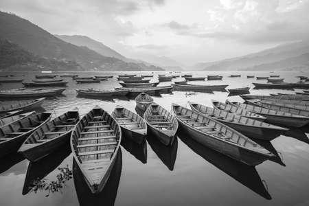 traquility: Wooden boats on Phewa lake in Pokhara, Nepal
