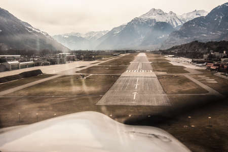 cessna: A propeller airplane landing in Sion airport in the middle of the snow covered Alps mountain range in Valais, Switzerland Editorial