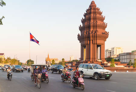nom Penh, Cambodia - January 14 2015: Cars and motorcycles drive around the Independance monument in downtown Phnom Penh. 新聞圖片
