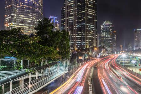 비즈니스 지구의 은행, 호텔 및 고급 쇼핑몰 (Jalan Sudirman)이 줄 지어있는 인도네시아 수도의 주요 도로를 따라 자카르타의 밤 교통. 에디토리얼