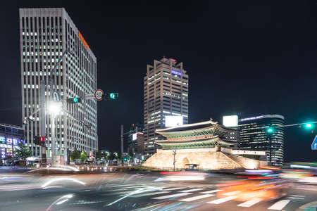 SEOUL, SOUTH KOREA - SEPTEMBER 8 2015: Traffic, captured with long exposure, rushes along the Sungnyemun Gate which is a remain of the old Seoul fortress in the heart of the city.
