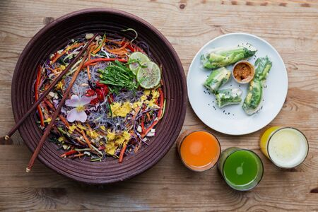 noodle bowl: Salad noodle bowl with threeg glasses of juice and a side dish of spring rolls