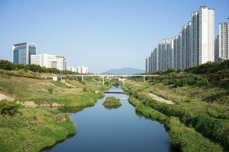 natural setting: Apartment buildings with streem and and grassland area in a natural setting Stock Photo
