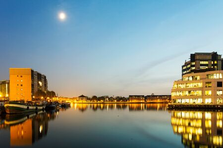 katherine: beautiful view of houses and buildings on St Katherine Docks at night time with moon shining
