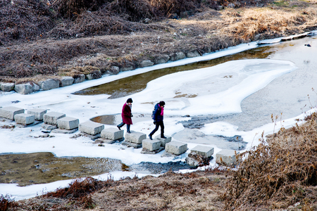 icey: SEOUL, SOUTH KOREA, - FEBURARY 03, 2016 - two women walking across an icey river on a cold winter day