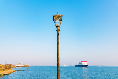 lamp post: Lamp post with blue sky ocean and ship in the background