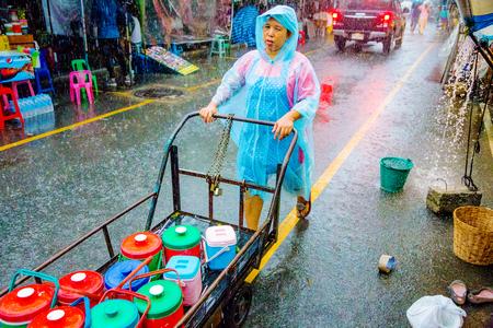 2014 년 6 월 29 일, 방콕에서에서 유명한 시장은 Chatuchak 주말 시장에서 몬 순 계절 동안 장바구니를 추진하는 작업의 방콕, 태국 -6 월 29 일 : 비오 장면