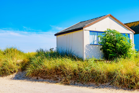 hengistbury: Beach hut covered with grass on a sunny day Stock Photo