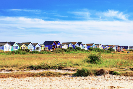 hengistbury: colorful beach huts with blue sky and grassland