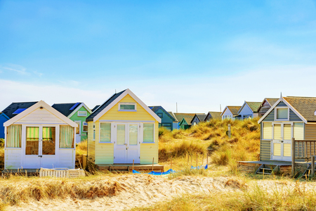 hengistbury head: Beach huts with grassland and blue sky