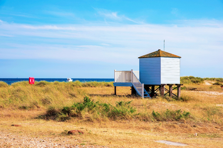 hengistbury: Beach hut isolated in grassland and ocean in the background