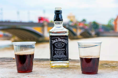 daniels: LONDON - AUGUST 25: An empty Jack Daniels whiskey bottle with two half filled cups on a wall by the River Thames in London on August 25th, 2016 in London