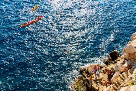 DUBROVNIK, CROATIA - SEPTEMBER 22: View of a rocky beach with tourists and kayakers in the sea on September 22, 2016 in Dubrovnik