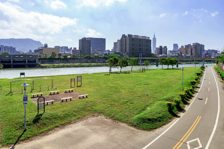 Riverside park cycling path and cityscape in Taipei Stock Photo