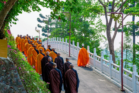 Monks walking along a small street with nature Stock Photo - 71036933