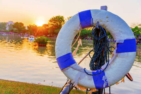 Life buoy with out of focus lake and sunset in the background in Chatuchak park Stock Photo