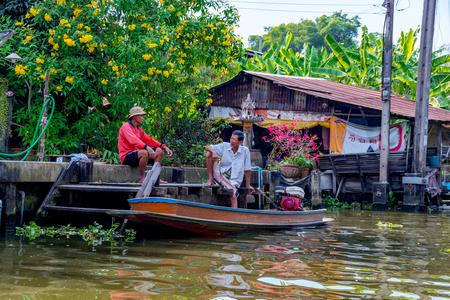 BANGKOK, THAILAND - FEBRUARY 05: Thai people relaxing and talking outside a riverside house in a rural area of Bangkok February 05, 2017 in Bangkok