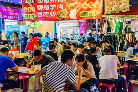 come in: TAIPEI, TAIWAN - JUNE 19: This is a night scene of people eating in Raohe street night market, a famous market where many locals and tourists come to eat and shop on June 19, 2017 in Taipei