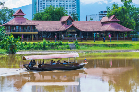 CHIANG MAI, THAILAND - JULY 29: This is a view of a tourboat and riverside buildings along the famous Ping river on July 29, 2017 in Chiang Mai Sajtókép