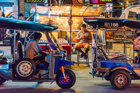 CHIANG MAI, THAILAND - JULY 30: Night market street scene of tuk tuks with stalls in the background in the famous Chiang Mai night bazaar on July 30, 2017 in Chiang Mai Stock Photo - 89298794