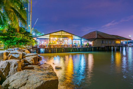 These are waterfront seafood restaurants where people come to eat at night in Sriracha Stock Photo