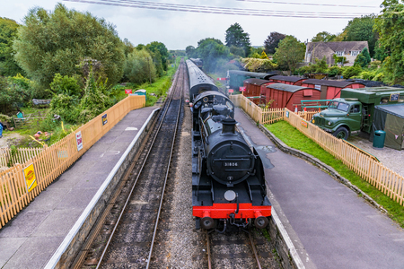 CORFE, UNITED KINGDOM - SEPTEMBER 08: This is an old British steam train passing through the medieval village of Corfe on September 08, in Corfe