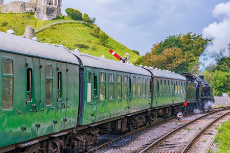CORFE, UNITED KINGDOM - SEPTEMBER 06: This is a traditional British steam train passing through the medieval town of Corfe on September 06, in Corfe Standard-Bild - 90728097