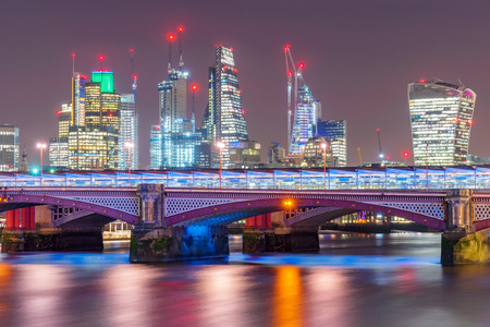 City of London skyline along the River Thames at night