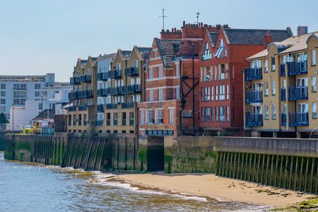 LONDON, UNITED KINGDOM - APRIL 20: River Thames waterfront houses and flats in the Docklands area near Canary Wharf on April 20, 2018 in London Editorial