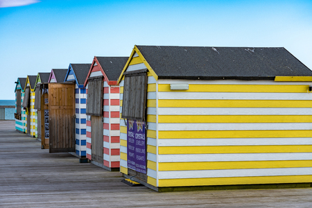 HASTINGS, UNITED KINGDOM - JULY 29: Colourful beach huts on Hastings Pier, a popular holiday destination on July 29, 2019 in Hastings