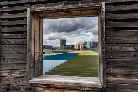 FRANKFURT, GERMANY - SEPTEMBER 25: View of colorful rooftop through a wooden window frame at the Skyline Plaza sky garden on September 25, 2019 in Frankfurt