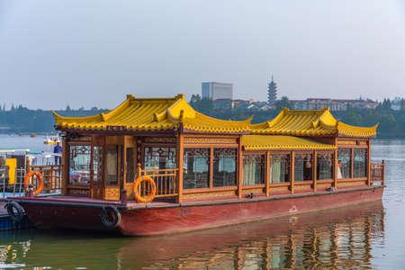 NANJING, CHINA - NOVEMBER 09: Traditional Chinese tour boat docked along Xuanwu Lake waiting for passengers on November 09, 2019 in Nanjing