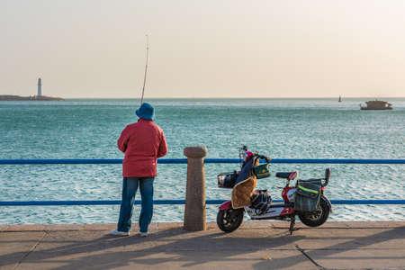 QINGDAO, CHINA - NOVEMBER 13: Local fisherman fishing along the waterfront area near May Fourth Square on November 13, 2019 in Qingdao Editorial