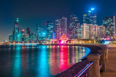 QINGDAO, CHINA - NOVEMBER 13: Night view of the Qingdao financial district skyscrapers along the waterfront on November 13, 2019 in Qingdao Editorial
