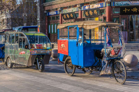 TIANJIN, CHINA - NOVEMBER 18: Rickshaws waiting for passengers outside the Tianjin Ancient Culture Street on November 18, 2019 in Tianjin Editorial